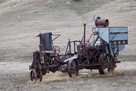 An antique tractor and hay bailer. photo