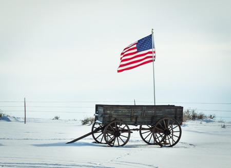 An American flag flies above an antique wagon. Stock Photo