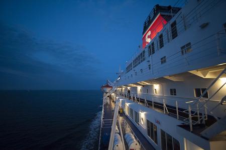 Foto zeigt eine Seite des großen weißen moderne Fähre, mit sichtbaren leuchten Decks und einem roten Trichter, marineblau Nacht Himmel und ruhiger See Editorial