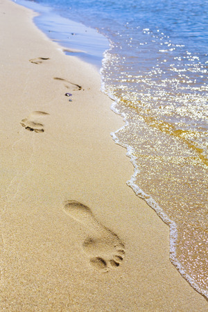 footprints in sand: Clear footprints on the beach by the sea, visible yellow sand and blue sea