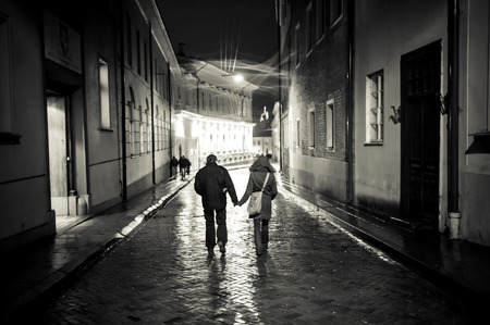 A young couple holding hands walking at night in the old town street, cobbled street wet from the rain, autumn evening Editorial