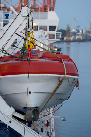 White and red lifeboat, visible ropes and elements of the lift photo