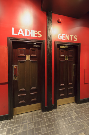 woman toilet: Entrance to the WC,  toilets in the restaurant, separate for ladies,women and gents,menon the red wall, dark brown door