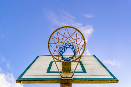 targetting: Old style basketball basket with the board, shot from bottom with visible blue sky