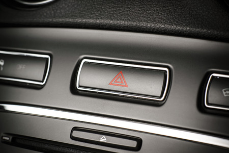 flashers: Button of vehicle, car hazard warning flashers button with visible red triangle, visible  fragment of control panel, visible red triangle emergency symbol