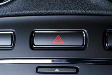 Button of vehicle, car hazard warning flashers button with visible red triangle, visible  fragment of control panel, visible red triangle emergency symbol  photo