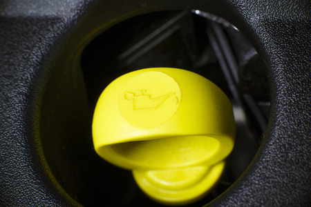 Yellow Engine oil dipstick in car vehicle engine, with visible yellow symbol  photo