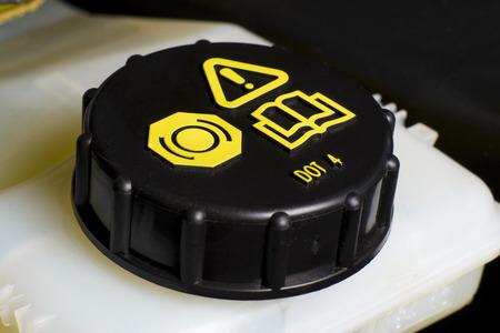 Die Wartung der Fahrzeuge Fragment, Brems-und Kupplungsflüssigkeit prüfen Kappe mit schwarzer Kappe und gelbe Warninformation Standard-Bild
