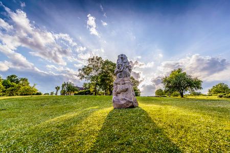 Idyllische Landschaft des Parks mit Steinskulptur in der Mitte, gegen Sonne geschossen, sichtbare grüne Bäume, grünes Gras mit kleinen weißen Blüten im Hintergrund Sonnenstrahlen, blauer Himmel und Wolken Photo scharf in der Öffentlichkeit stattgefunden Standard-Bild
