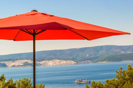 Red Terrasse, Garten Regenschirm gegen blaues Meer und wolkenlosen Himmel, sichtbar Küste, Schiff in der Ferne Standard-Bild