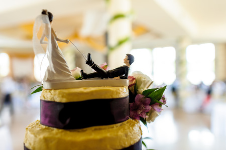 Fragment of yellow and purple wedding cake with funny decoration symbolizing groom pulled by leg on a leash by bride, wedding hall in background  photo