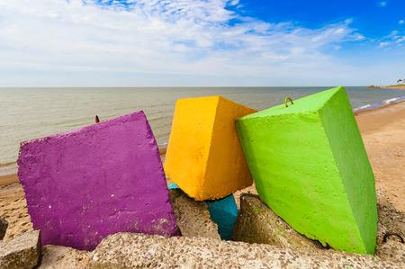 Drei verschiedene Farben - lila, gelben und grünen Wellenbrecher Betonblöcken am Strand, in der backgroundblue wolkenlosen Himmel, gelber Sand und die Küste