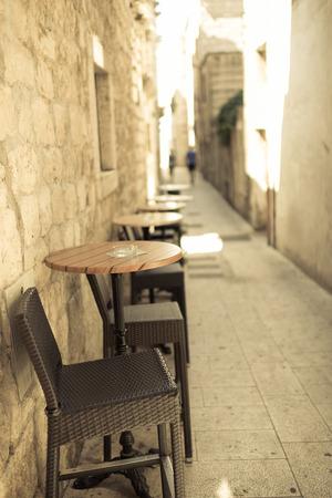 Schmale Straße in der Altstadt mit alten Sandsteingebäude, im Vordergrund caffee Tisch und Stühle, Outdoor-Foto