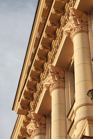 Fragment des klassischen oder neoklassischen Gebäude mit Säulen und feinen Kapitellen, mit warmen Sommer Sonnenlicht, blauer Himmel sichtbar beleuchtet Standard-Bild