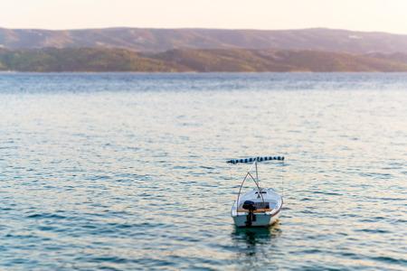 Sommer-Foto von Einzel Boot im Meer, im Hintergrund sichtbaren Berge und Inselküste, illeminated durch Sonne Licht, Tilt- und Shift-efects