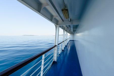 Fragment von Deck auf Schiffen oder Passagierfähre mit sichtbaren Geländer und blaues Meer, im Hintergrund wolkenlosen Sommerhimmel