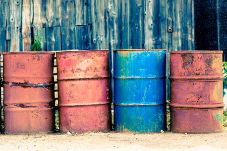 Photo presents four old used rust barrels for oil, petroleum, crude oil, mineral oil or petrol, three barrels are red and one is blue  In background visible wooden storehouse, warehouse  photo