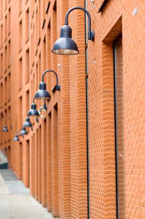 perspectiva lineal: Ataque frontal de fragmentos visibles moderno edificio de ladrillo rojo ith de las ventanas y las farolas negro, la perspectiva lineal