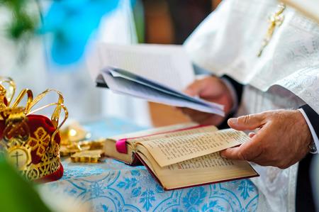 Foto präsentiert heilige Bibel, Krone und Fragment der Hand der orthodoxen Priester Crown ist symbollic in der orthodoxen Kirche Trauung erkennbare Körperteile - Modell realease nicht erforderlich