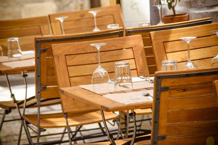 Foto präsentiert Altstadt Restaurant im Freien, sichtbare Holztisch und Stühle, Gläser und Wein galsses puy Kopf nach unten auf den Tischsets