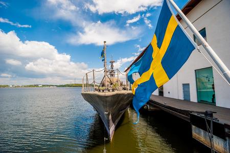 Blaue und gelbe Flagge weht in Schweden breese mit Kriegsschiff in harobour festgemacht, sichtbar im Hintergrund blauer Himmel und Wolken Standard-Bild