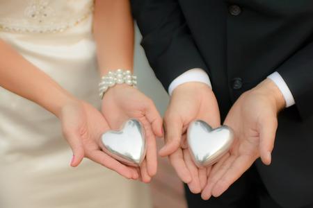 Mann und Frau, elegant gekleidet, trägt Hochzeitskleid, halten symbolischen silbernen Herzen in ihren Händen, softfocus, sichtbar unkenntlich Fragmente von Körper, Model-Release nicht erforderlich