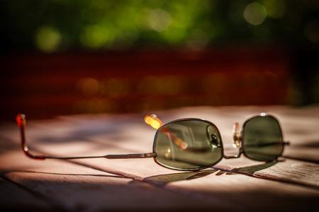 Gebrauchte Sonnenbrille im Ort des Sonnenlichtes auf braunen Holztisch, braun Fragment der Holzkonstruktion und grünen Blättern Standard-Bild