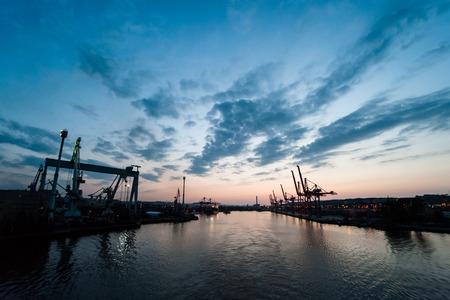 Dock Krane im Frachtterminal mit sichtbaren Formen von Behältern gegen Dämmerung Himmel Hintergrund, vivible Hafeneinfahrt und den Hafen
