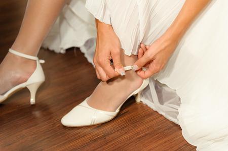 Junge Frau Befestigung weiße elegante Hochzeitsschuhe, sichtbar unkenntlich Fragmente der Körperteile - Arm, Hände, Beine, Füße, Model-Release nicht erforderlich