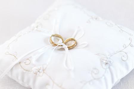 Zwei Hochzeitsringe auf embroided weißem Kissen durch weißen Band gebunden