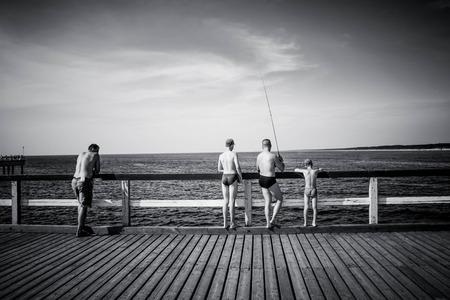 Foto präsentiert 4 Personen - 3 Männer und Kinder, alle stehen nach hinten, in Badeshorts, Angeln mit Angelruten, die auf Pier. Die Menschen sind unreognizable, Model-Release nicht erforderlich. Schwarz-Weiß-Foto.