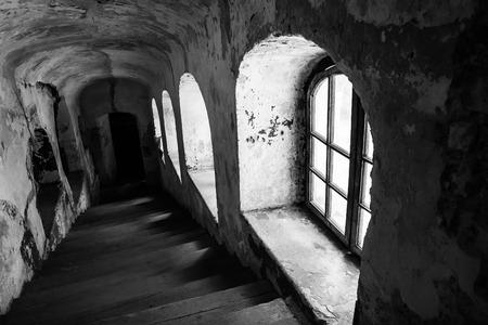 Holz staris im alten Gebäude, Kirche mit sichtbaren Fenster und beschädigte Wände und Putz, b & w Foto.