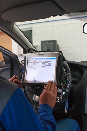 Servicemitarbeiter sitzt im Inneren Auto-Programmierung Computer und Überprüfung der Diagnose oder Elektrosystem Sichtbare Arme und Hände - unkenntlich Körperteile, Model-Release nicht requairs