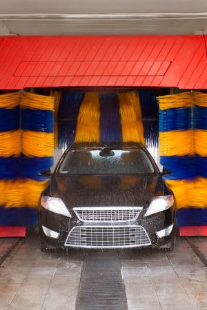 Auto in Waschanlage gewaschen, blau und gelb rotierenden Bürsten sichtbar; unrecognizible Marke und Modell Etiketten, Model-Release nicht erforderlich Standard-Bild