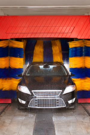 Car being washed in automatic car wash, rotating blue and yellow brushes visible; unrecognizible make and model labels, model release not required  photo