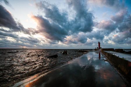 Fragment aus Beton, nass von regen Wellenbrecher mit sichtbaren Raugh Meer, dramatischen Sonnenuntergang und Wolken, sichtbar Sturmlaterne, Leuchtturm