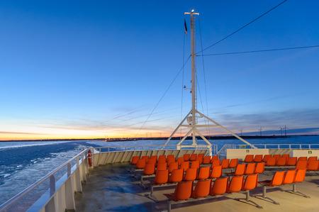 Orange im Freien Liegestühle am Fährschiff vor Sonnenaufgang fotografiert, auf der Fähre Segeln im gefrorenen Meer Standard-Bild