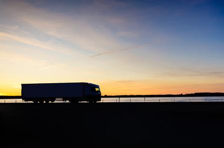 Silhouette des schwarzen LKW-Container vor Sonnenuntergang Hintergrund Platz für Text trägt Standard-Bild