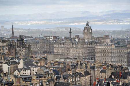 Fragment der alten Stadtzentrum in Edinburgh, Hauptstadt von Schottland, mit charakteristischen hellbraunen Sandsteingebäuden, sichtbare Glockenturm und das Meer in der Ferne Standard-Bild