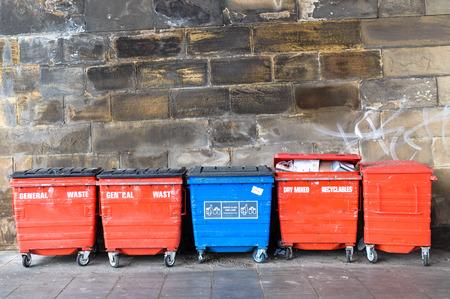 Eine blaue und vier rote Straße Mülltonnen, Abfallbehälter, Papierkörbe, sichtbaren Fragment der Mauer