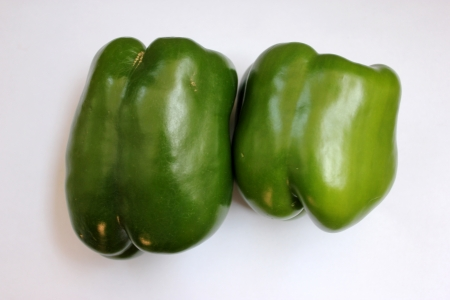 drooping: Green bell pepper, Capsicum annuum, annual herb Producing large bell shaped drooping fruits, INITIALLY green, turning yellow and finally red Used in salads, stir-fries and pizza toppings Stock Photo