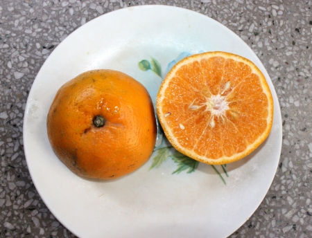 Kinnow, Citrus reticulata, a possible hybrid between King Tangor and Willowleaf mandarine, commonly cultivated in India and elsewhere, orange-yellow slightly depressed fruits with closely packed segments  Sweet with distinctive flavor Stock Photo - 24426135