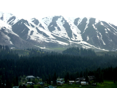 seen: Snow covered Apharwat Mountain Slopes as seen from Gulmarg meadow with hotels Stock Photo