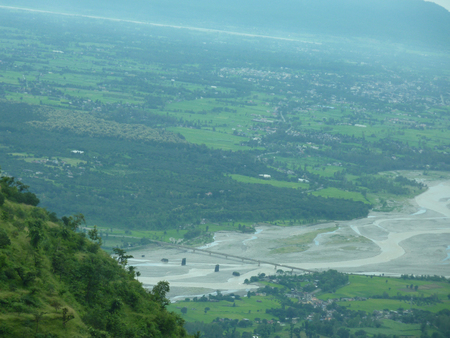 flood area: View of Chakrata, Uttarakhand, clicked from mountain road above with habitations, flood plains and forest areas, with distant mountain ranges