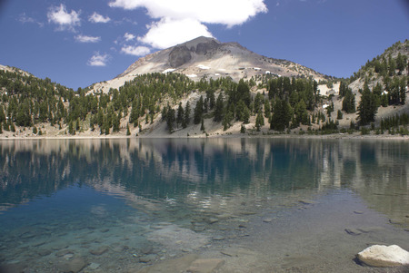 helen: Lake Helen, Lassen Volcanic National Park, California, USA, a glacial lake below Lassen peak in Shasta Cascade region, with crystal clear water surrounded by snow covered slopes with conifer trees Stock Photo
