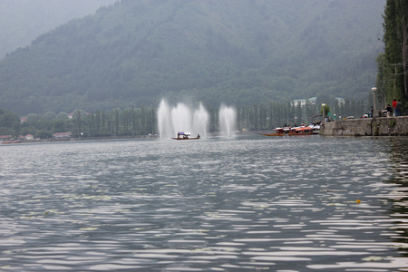 poplar  banks: Dal Lake, Srinagar, Kashmir, with beautiful Boulevard road winding along banks, lined by poplar trees, Shankeracharya hill in the background, tall fountains Stock Photo