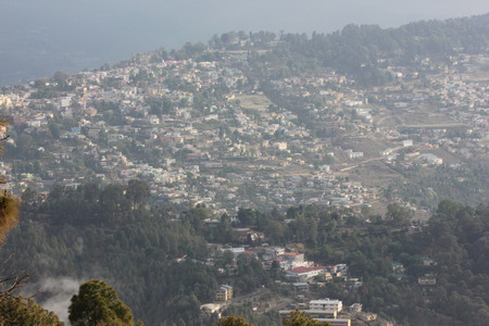 closer: View of Nainital, with buildings, roads, Naini lake, forested mountain slopes, closer view of pine trees.