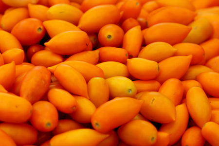 produced: Oblong orange yellow cherry tomatoes, Solanum lycopersicum, small onlong orange yellow cherry tomatoes with pointed end, produced on vines, used in salads and recipes.