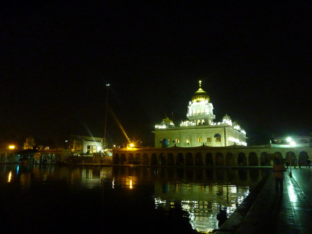 gurudwara: Night scene of Gurudwara Bangla Sahib, New Delhi, with impressive building and holy sarovar, a place of worship for pilgrims from all parts of the World. Stock Photo