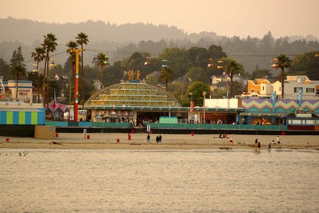 thronged: Santa Cruz Bay area in California, USA, thronged by visitors with parked boats and ships, majestic buildings, rows of palms and play areas.